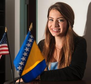 Medina Spiodic, a native of Bosnia who is a student at the University of Illinois, sits near a U.S. flag and Bosnian flag, at the International Studies Building in Champaign on Friday, Sept. 27, 2013.