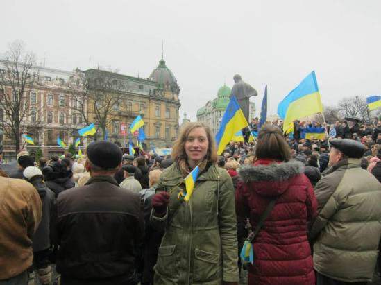 Areta Kovalsky holding the Ukrainian flag among a crowd of people also holding the Ukrainian flag