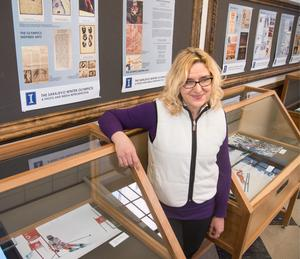 Sanja Koric stands Friday in front of an exhibit about the 1984 Winter Olympics in Sarajevo, Yugoslavia, at the University of Illinois Main Library. (Photo courtesy of John Dixon/The News-Gazette)